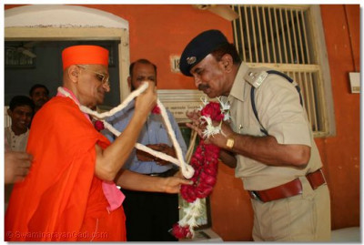 Acharya Swamishree gives a garland to the chief police officer