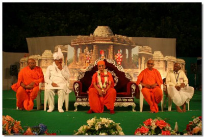 Acharya Swamishree gives darshan on stage, with Shree Jitendrabhai Sukhadiya, the 2 mahants of Shree Swaminarayan Mandir Varodara, Shree Nityaprakashdasji Swami and Shree Harikeshavdasji Swami, and a leading disciple from Varodara