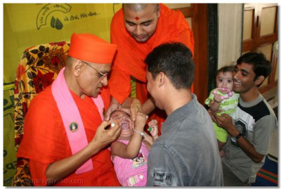 Acharya Swamishree administers the polio vaccine