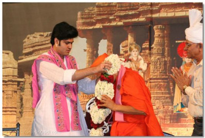 Shree Vrajrajkumarji offers a garland to Acharya Swamishree