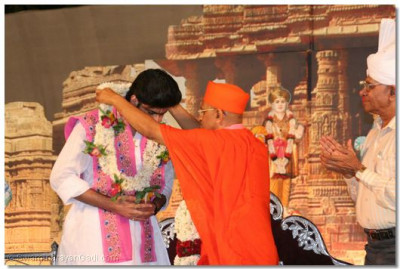 Acharya Swamishree gives a garland of flowers to Shree Vrajrajkumarji