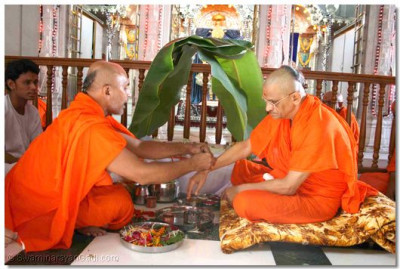 During the Mahapooja ceremony, the sacred thread is tied on Acharya Swamishree's right wrist