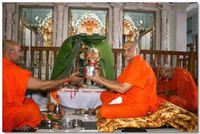 Acharya Swamishree lifts the coconut and urn, representing the world and its controller, i.e. the supreme God, and places it onto the ceremonial platform