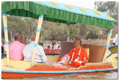 Acharya Swamishree gives prasad to the fish in the water