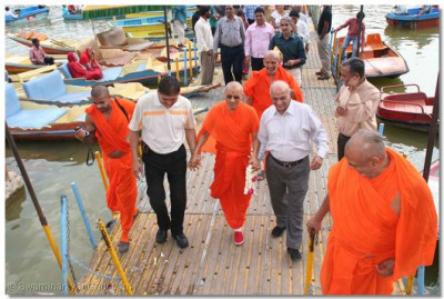 Acharya Swamishree is led from the boat to the edge of Lake Nakki