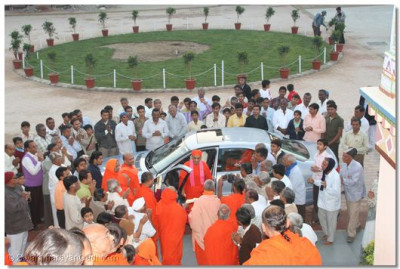 Acharya Swamishree is greeted by sants and disciples at the footsteps of Maninagar Temple