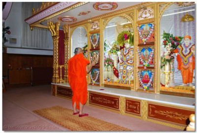 Acharya Swamishree performs aarti to the Lord at Shree Swaminarayan Mandir London, before departing for the airport