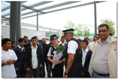 A bouquet of flowers is presented to the chief police officer at the airport for arranging the special police escort for Acharya Swamishree from the Temple to the airplane