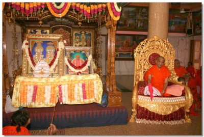 Lord Swaminarayan, Jeevanpran Shree Abji Bapashree and Jeevanpran Swamibapa are seated on a grand swing whilst sants sing devotional songs