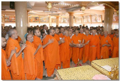 Acharya Swamishree, sants and disciples perform aarti to mark the end of the 24 hour dhoon