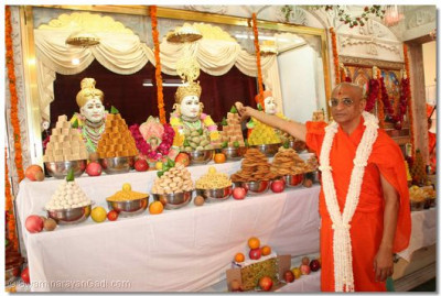 Acharya Swamishree offers a sweet to the Lord