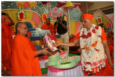 Acharya Swamishree offers the cake to Shree Harikrishna Maharaj
