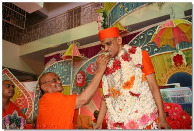 Sadguru Shree Akhileshwardasji Swami offers some cake to Acharya Swamishree