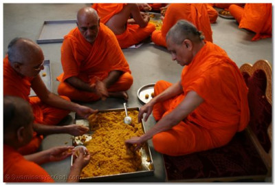 Acharya Swamishree makes ladus; sweet balls of wheat, sugar and ghee, which will be offered to the Lord