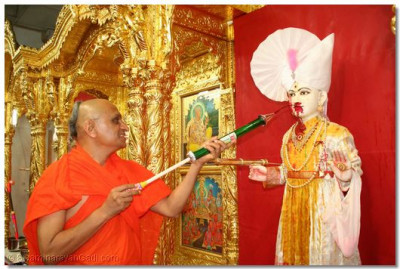 Lord Swaminarayan being sprayed with coloured water