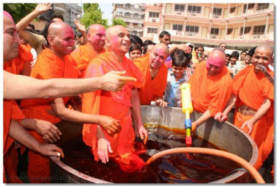 Acharya Swamishree prepares to shower everyone with coloured water