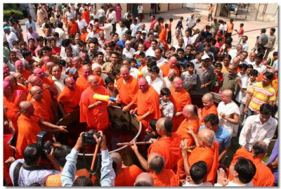 Acharya Swamishree showers everyone with coloured water