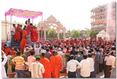 Acharya Swamishree sprays coloured water over disciples