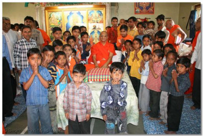 Acharya Swamishree gives blessings and assistance to orphaned children of the region