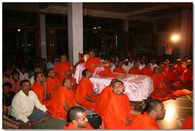 Acharya Swamishree, sants, and disciples watch the performance