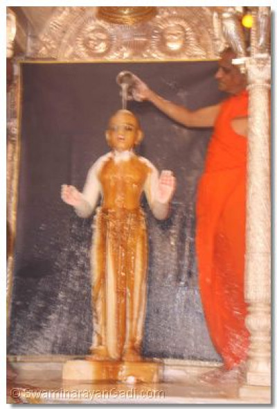 Lord Swaminarayan being bathed in honey