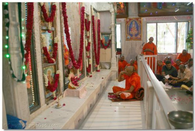 Acharya Swamishree chants the supreme Swaminarayan mantra as He places a flower petal at the Lord's divine lotus feet