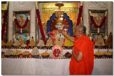 Acharya Swamishree lovingly offers a sweet to supreme Lord Shree Swaminarayan – Shree Ghanshyam Maharaj