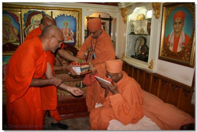 Sadguru Shashtri Shree Jitendriyapriyadasji Swami presents Shree Hariprasad Swami with prasad