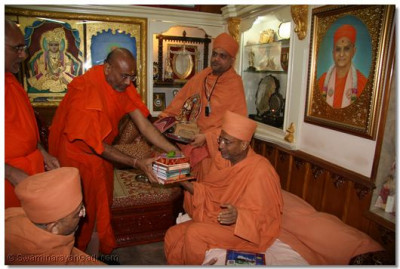 Shree Nityaprakashdasji Swami, Mahant of Shree Swaminarayan Temple Varodara, presents some recent publications of Shree Swaminarayan Gadi Sansthan to Swami Hariprasadji Maharaj
