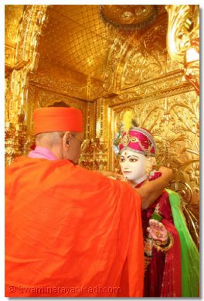 Acharya Swamishree garlands Shree Ghanshyam Maharaj immediately after entering the Temple