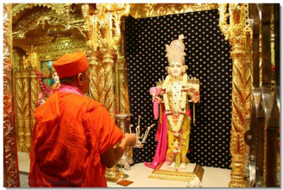 Having offered a flower garland to Shree Ghanshyam Maharaj, Acharya Swamishree performs aarti