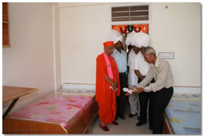 Acharya Swamishree is given a guided tour of the facilities