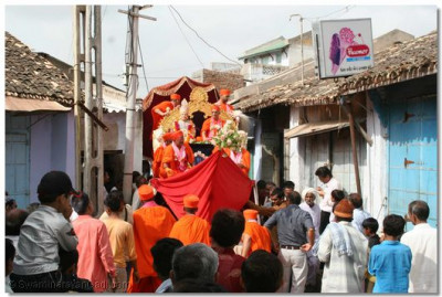 The procession passes through the narrow streets of the village