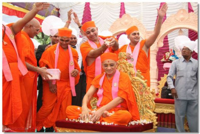 The sants perform poojan with the gold and silver flowers and petals to Acharya Swamishree