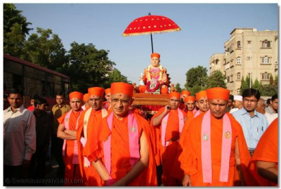 Acharya Swamishree leads the procession in which Jeevanpran Swamibapa is carried in a palanquin by His loving sants
