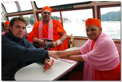 Acharya Swamishree offers prasad to the pilots of the boat