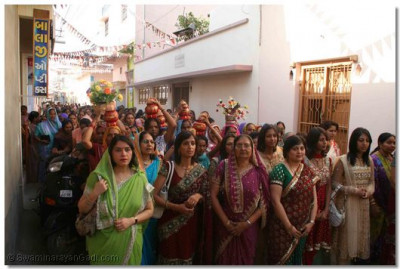 Disciples take part in the welcoming procession, and sing devotional songs as they walk from the Mandir to the assembly marque
