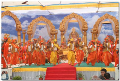 As the procession arrives at the assembly marquee, young disciples perform a welcoming dance and ceremonially lead Acharya Swamishree to the stage