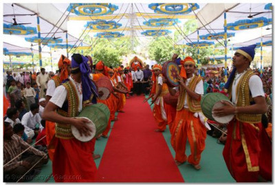 Dancers and musicians perform as Acharya Swamishree arrives at the assembly marquee