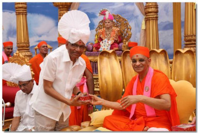Acharya Swamishree gives prasad to Shree Jadavjibhai of the Anchor Group