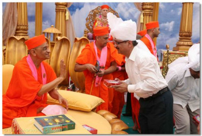 Acharya Swamishree blesses Shree B D Changrani, Chief Executive of the Union Bank in this region of Kutch