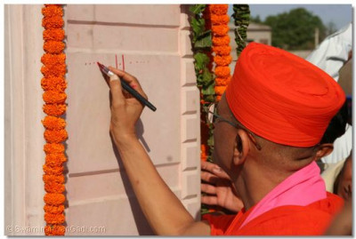 Acharya Swamishree inscribes the sacred name of the supreme Lord Swaminarayanbapa Swamibapa on the new grand gate of Madhapar