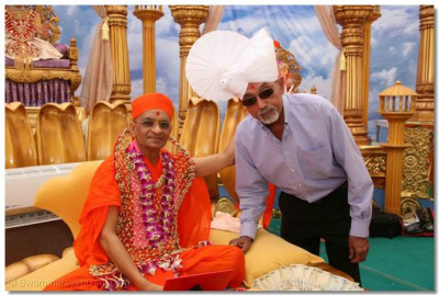 Acharya Swamishree blesses the President of the Madhapar MSP High School, Shree Karsanbhai