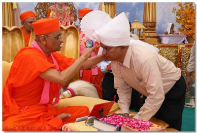 Acharya Swamishree blesses Shree Yogesh Roa, assistant engineer of PGVCL