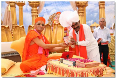 Acharya Swamishree presents prasad to the Minister of Gujarat, Shree Vasantbhai Aahir
