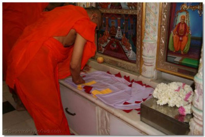 Acharya Swamishree scribes the sacred name of the Lord on the new flags that are then raised on the roof of the Mandir