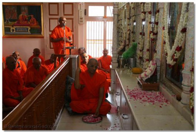 Acharya Swamishree places flowers at the lotus feet of the Lord whilst sacred verses are recited