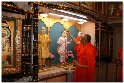 Acharya Swamishree starts the patotsav ceremony by offering chandlo to Shree Ghanshyam Maharaj at Jeevanpran Swamibapa's room