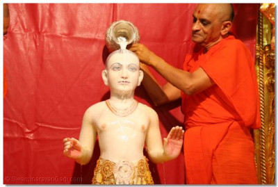 Acharya Swamishree bathes Lord Swaminarayan with milk