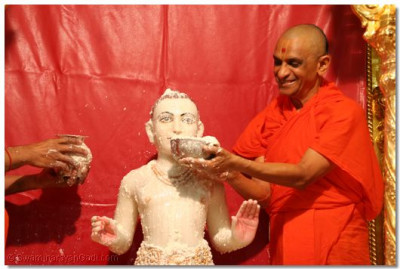Acharya Swamishree offers yogurt to Lord Swaminarayan